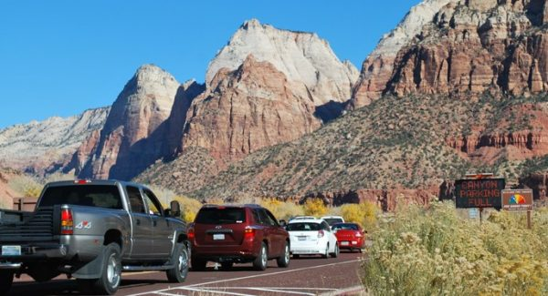 A line of vehicles waits outside the entry gate to Zion National Park.