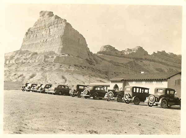 Cars line up at Scotts Bluff National Monument Visitor Center, Scotts Bluff in background.