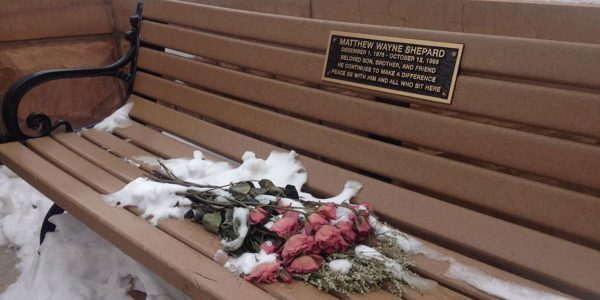 Matthew Shepard memorial bench with bouquet of roses.