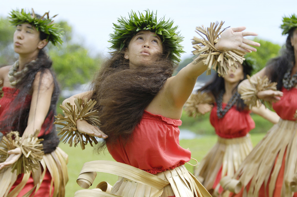 Native Hawaiian hula dancers in red and beige perform a traditional hula dance.
