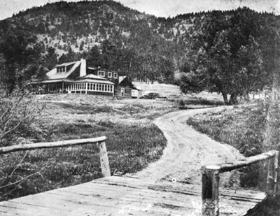 View up a dirt road to the main building of the McGraw ranch, a two story ranch-style building with an enclosed porch, rustic architecture, and a sweeping view of lumpy ridge in the background.