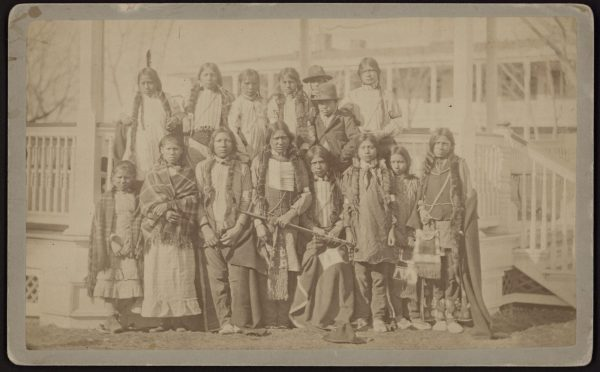 A group of Northern Arapaho and Shoshone youth on the day they were admitted to Carlisel Indian School. The students are grouped together, looking nervous but stoic. They wear traditional dress including feathers, blankets, and other Native American garb.
